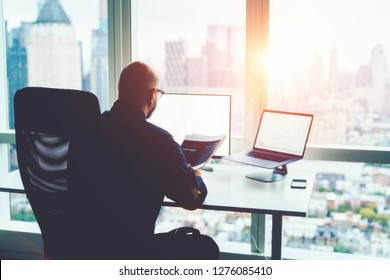 Rear view of man financial specialist studying theory and practice blockchain technology. Male broker sitting front office computer with graphs statistics of stock exchange. Earnings on raising quotes