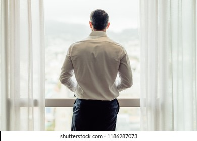 Rear view of man in formal wear standing at hotel room window and looking outside. Business man looking at the cityscape from hotel room window.