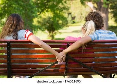 Rear view of a man with girlfriend while holding hands with another woman in the park