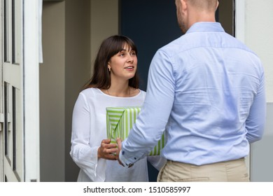 Rear View Of A Man Giving Gift Box To His Smiling Neighbor Standing At Doorway