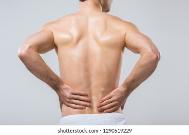 rear view of man having back pain, isolated on grey