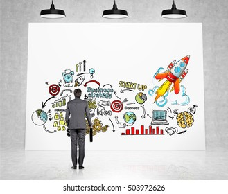 Rear view of man holding his suitcase and standing near concrete wall with colorful business sketches on it. Concept of planning. 3d rendering.