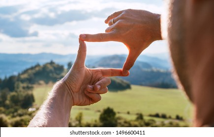 Rear view of Man looking at mountain landscape framing with fingers, searching for best image composition as he hiking over the mountain range. Landscape photographer or moviemaker occupation concept.