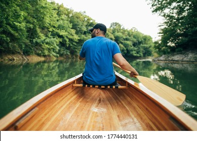 Rear view of man paddling canoe in the forest lake