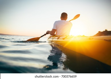 Rear view of man paddling kayak. Paddling the canoe at sunset. Kayaking, canoeing, paddling