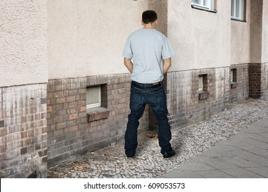 Rear View Of A Man Peeing On The Wall Of A Building