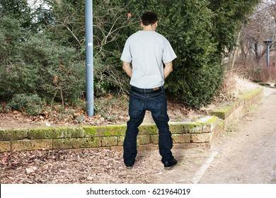 Rear View Of A Man Peeing Outside