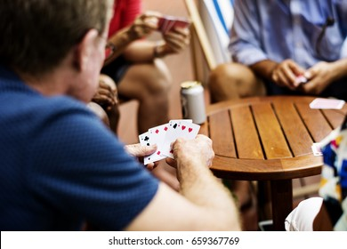Rear view of man playing card game with friends