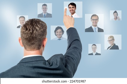 Rear view of man pointing coworkers picture on screen