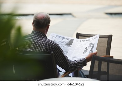 Rear view of man reading news in local newspaper