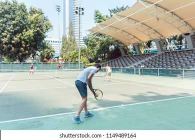 Rear view of a man ready to serve while standing behind the baseline of a professional tennis court during doubles match