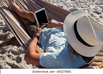 Rear view of man relaxing on hammock and using digital tablet on the beach