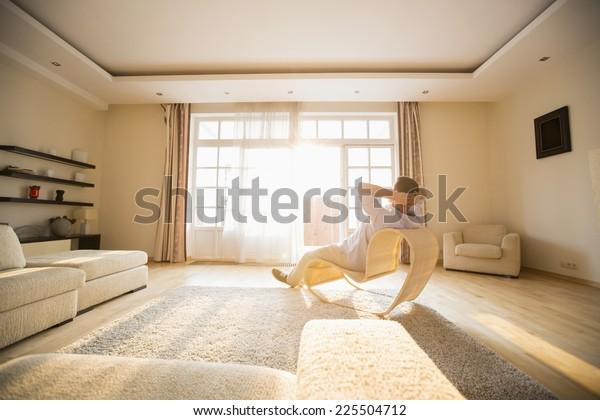 Rückblick auf den Mann entspannen auf modernen Stuhl zu Hause