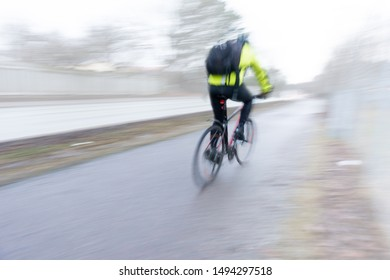 Rear view of man with rucksack on modern red bicycle in blurred motion on gloomy rainy day