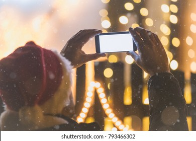Rear view of man with santa claus cap taking a photo of christmas lights decoration with his smartphone