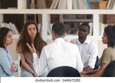 Rear view man sharing problems with diverse group at therapy session, male therapist, psychologist speaking with patients at meeting, addiction treatment, coach training staff, team building activity