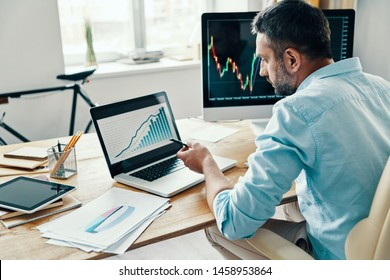 Rear view of man in smart casual wear analyzing stock market data while sitting in the office
