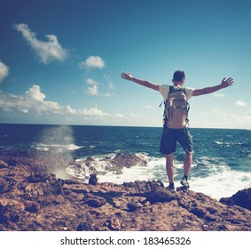 Rear view of man spreading arms and watching the ocean