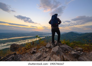 Rear view of man standing on the cliff to watch sunrise over mekong river in Nong Khai, Thailand
