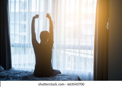 Rear View Of A Man Stretch His Hands After Waking Up In Bed At Morning