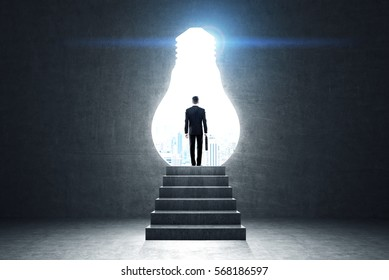 Rear view of a man with a suitcase standing on a stairs near a light bulb shaped opening in a black wall. Toned image.