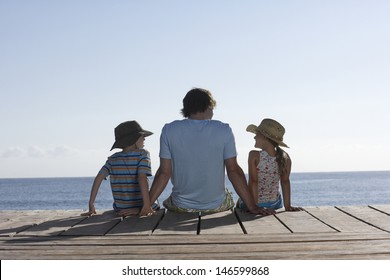 Rear view of a man with two children sitting on jetty