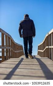 Rear view of a man walking away on wooden boardwalk.