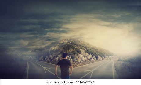 Rear view man walking in front of crossroad as road is split in two different ways. Choosing the correct path between left and right, failure or success. Difficult decision concept, important choice.