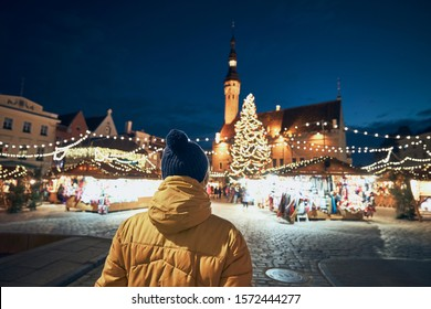 Rear view of man in warm clothing during night walk in city. Traditional Christmas market on Town Hall Square in Tallinn, Estonia.
