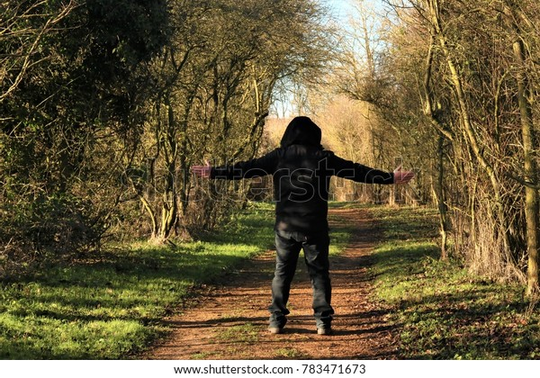 Rear view of man wearing hoody with arms outstretched on a countryside walk in the winter sun