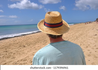 Rear view of man wearing straw hat and shirt to protect from the hot sun