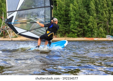 Rear view of man windsurfing in splashes of water