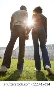 Rear view of a man and woman's figures holding hands while walking through London city on a sunny day.