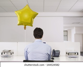 Rear view of a man working alone beside balloon in office