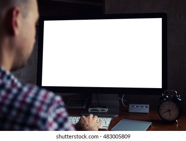rear view of a man working on computer at night. Monitor with blank screen
