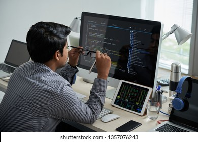 Rear view of IT manager sitting at his workplace with lots of gadgets and computers at office
