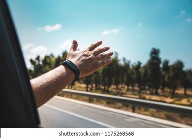 rear view of a man's arm waving from a moving car