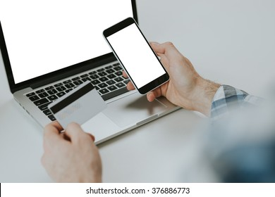 Rear view of man's hands using smart phone and credit card whith laptop. White screen mockup