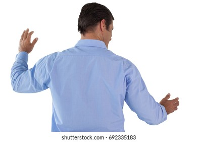 Rear view of Mature businessman gesturing while using invisible interface
