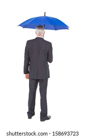Rear view of mature businessman holding blue umbrella on white background