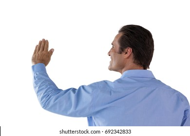 Rear view of mature businessman touching invisible interface against white background