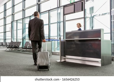 Rear view of mature businessman walking with his suitcase on his gate for boarding in airport