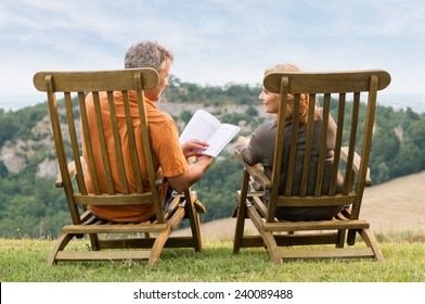 Rear View Of Mature Couple Sitting On Lounge Chair Reading Book