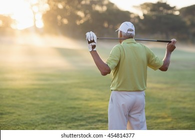 Rear view of mature golfer carrying golf club while standing on field