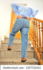 rear view of a mature man with lumbago pain climbing the stairs of his house