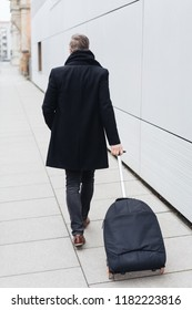 Rear view of mature man wearing black coat pulling suitcase along pavement