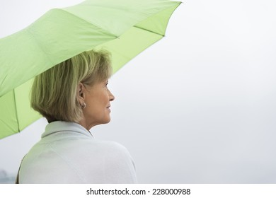 Rear view of mature woman with green umbrella looking away against clear sky