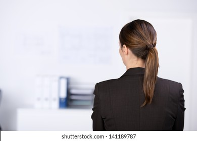 Rear view of mid adult businesswoman thinking in office