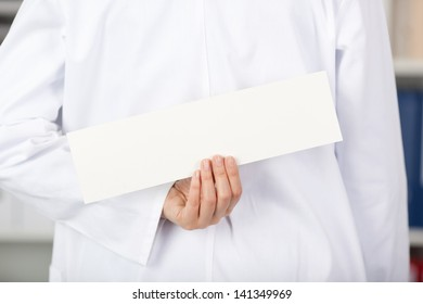 Rear view of mid adult female doctor holding blank label in clinic