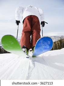 Rear view of mid-adult male on skis in Steamboat, Colorado.